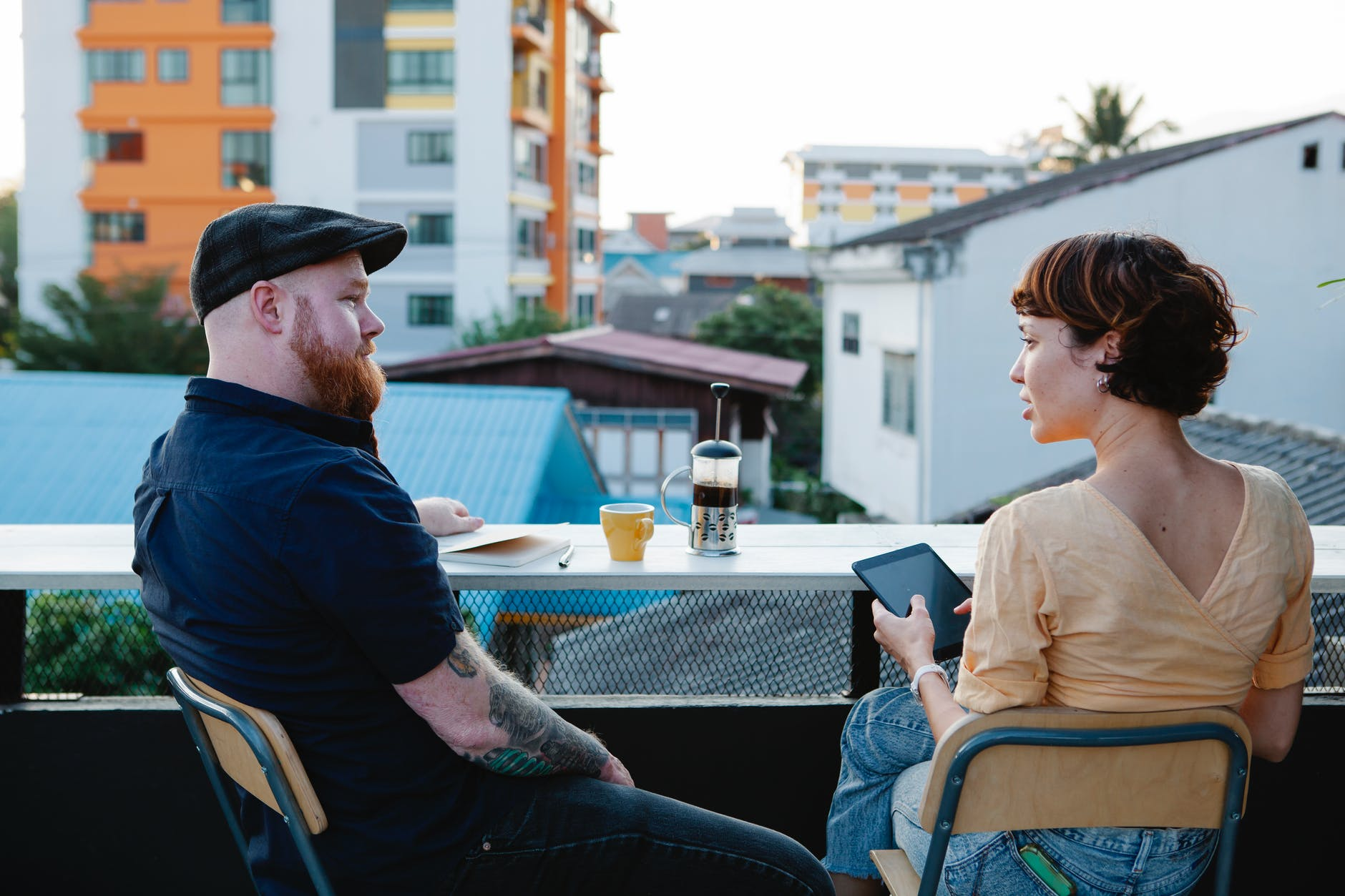 casual man and woman chatting and resting on terrace