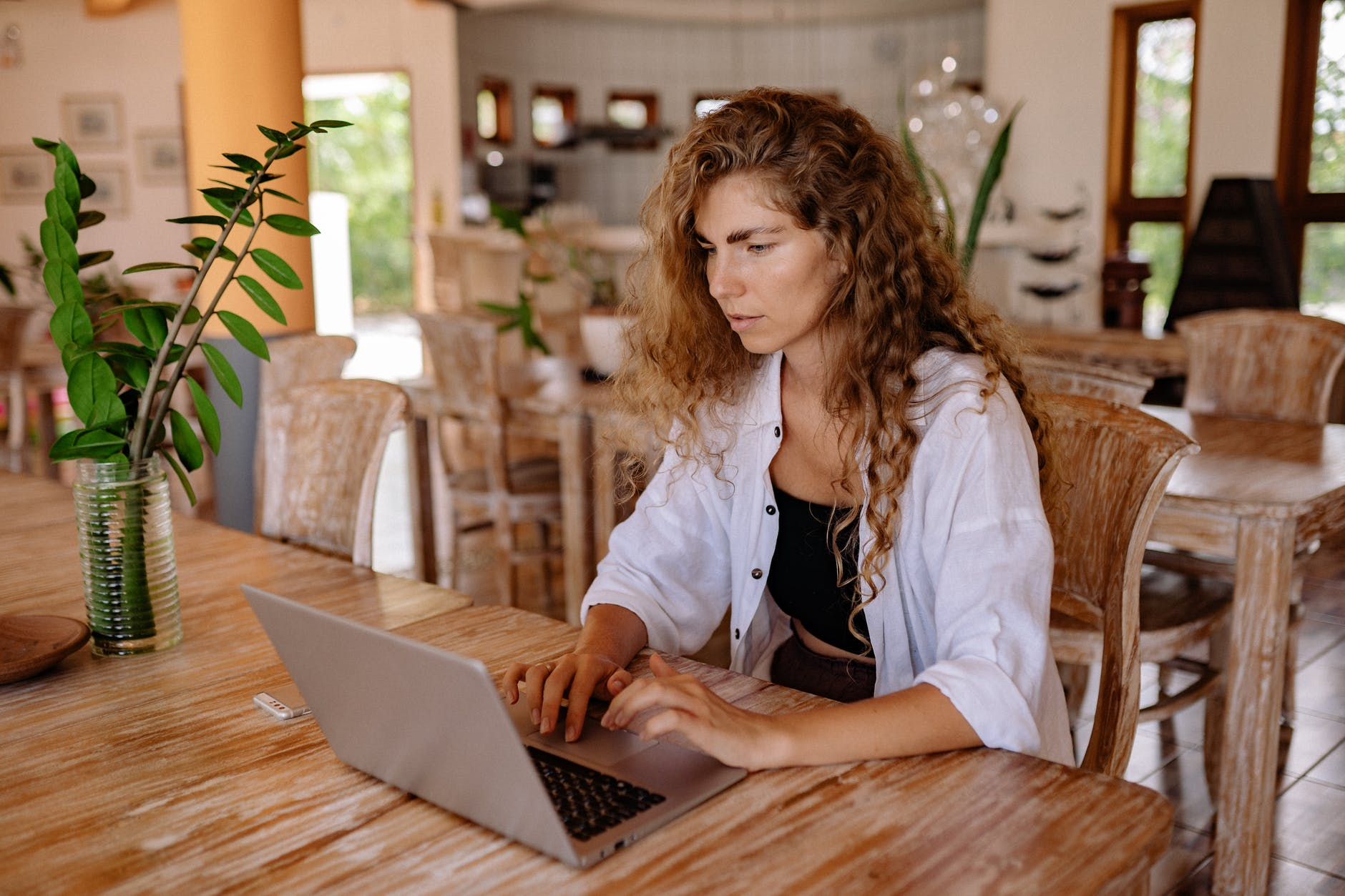 young woman using laptop at vintage cafe